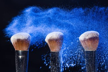 Make up, beauty and mineral cosmetics concept - powder brush on black background with blue powder splashed on it