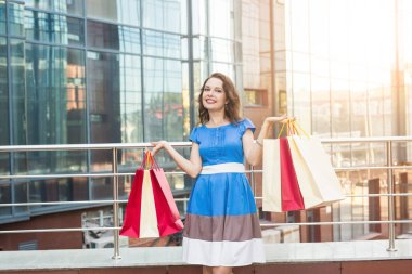 Purchase, sale and people concept - young happy smiling woman with shopping bags