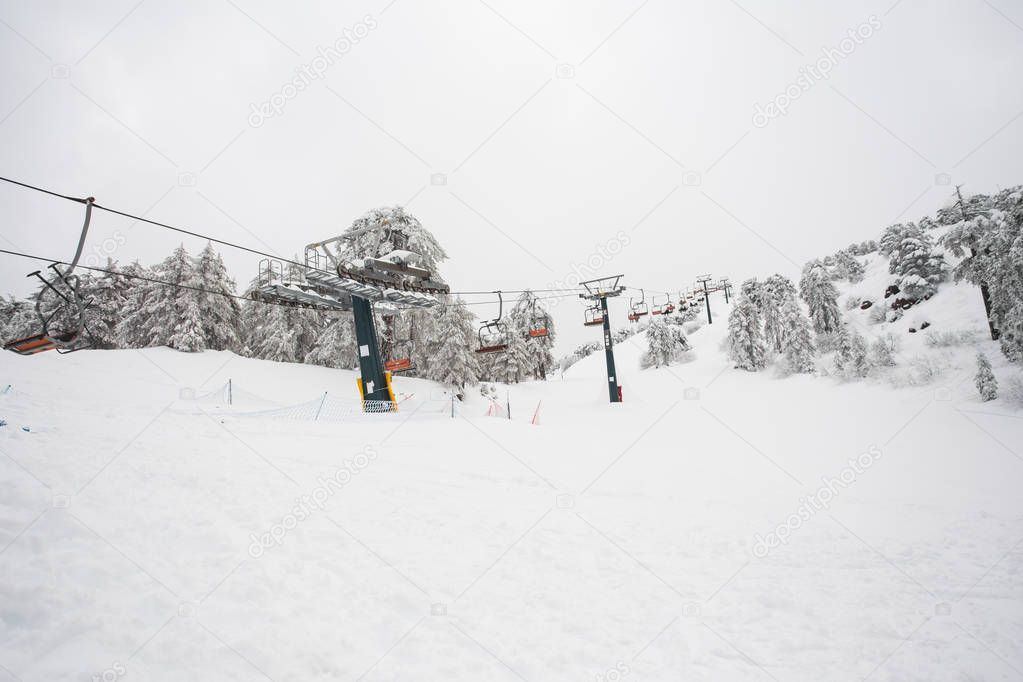 Ski lifts and cable cars going up the mountain bringing snowboarders to ski slopes.