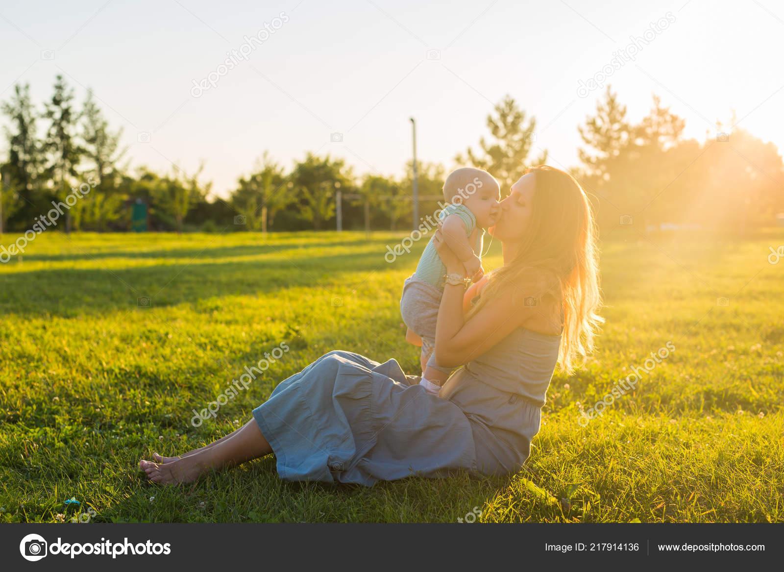 7c3e02295ad Mujer joven con el niño en el Prado en un día soleado. Familia feliz ...