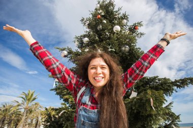 Christmas and holiday concept - Happy jumping woman over Christmas tree background
