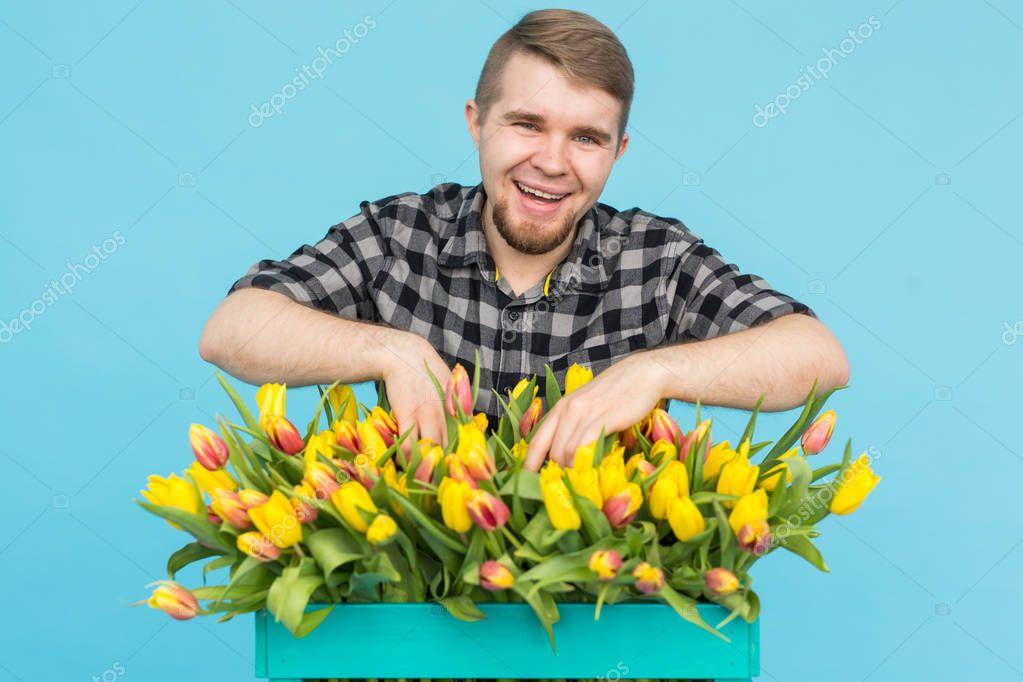 Handsome caucasian male gardener making a bouquet of tulips in blue studio.