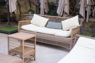 Outdoors lounge zone with brown wicker sofa and small coffee table