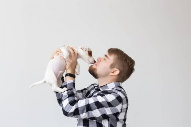 people, pets and animals concept - young man holding jack russell terrier puppy on white background