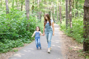 Family, children and nature concept - Portrait of attractive woman and little child girl walking together