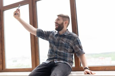 Side view of a positive handsome hipster guy and taking a selfie on a smartphone while sitting on a windowsill by a large window. Concept of gadgets and modern technologies.