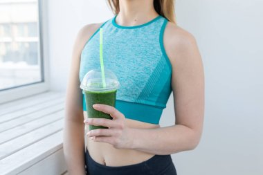 Healthy, fitness and detox concept - close up of young woman in sports wear with green smoothie indoors
