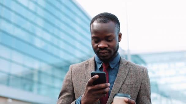 Afrikanischer Amerikaner tippt etwas in sein Smartphone, wenn er nach draußen geht. Geschäftsmann läuft durch das Flughafenterminal, benutzt sein Handy, trinkt Kaffee, druckt die Nachricht aus, lächelt. fröhliche Stimmung, glücklich sein