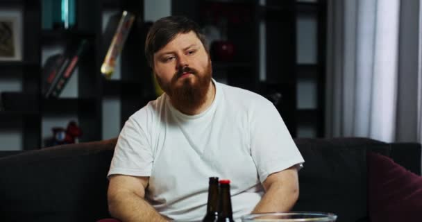 Bearded fat man drinks bear and watches TV with remote control in his hand, sitting at the table with pop-corn