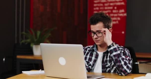 Portrét člověka škaredě mladých v brýlích, pracující v moderní kanceláři pomocí jeho laptop