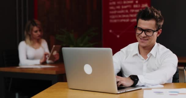 young businessman in glasses with laptop computer and paper working in office. Business, people, paperwork and technology concept. 4k, slow motion
