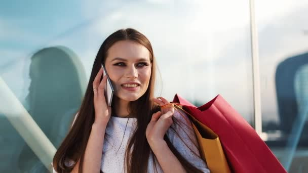 Sale, consumerism: Young woman with smartphones and shopping bags standing and talking near shopping centre