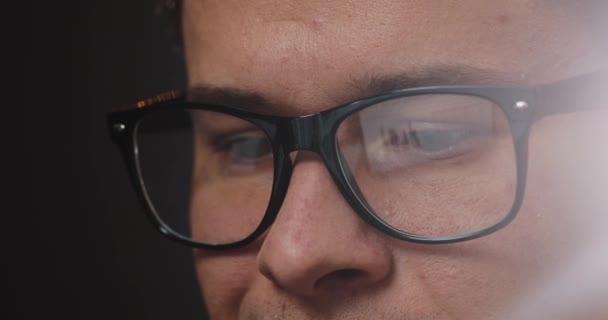 Detail z mans očí v brýlích, zatímco pracuje na přenosný počítač v kanceláři