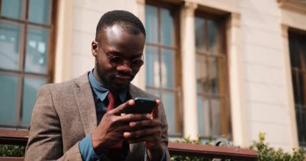 junger afrikanisch-amerikanischer Mann sitzt auf einer Bank und tippt auf seinem Smartphone. Geschäfts- und Lifestylekonzepte