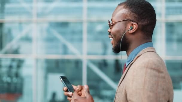 African American businessman in the sunglasses talking on the phone with headphones near the office building. Business, people, music, technology, leisure and lifestyle concept
