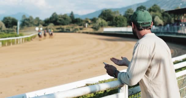 Koňské dostihy. Nadšenec diváka na koňské dostihy. Ten vsadil na koně. Sázkové výhry se smartphone ve svých rukou
