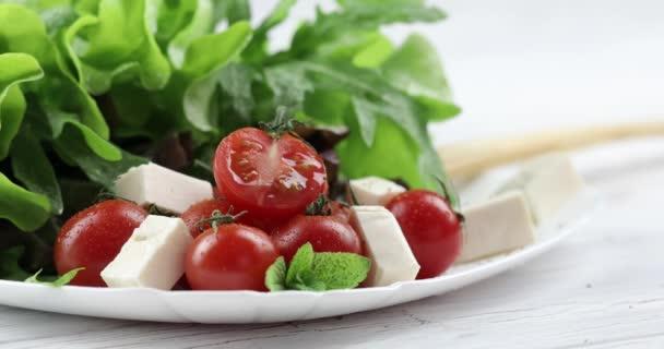 Vitamín salát z mozzarellou, cherry rajčaty a salátem. Muž ruce sypání aromatické koření