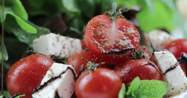 Vitamín salát od mozzarellou, cherry rajčaty a salátem je vyzdoben balzamikový ocet