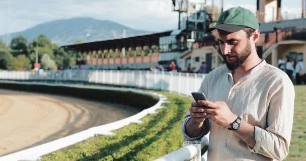 Koňské dostihy. Ten vsadil na koně s smartphone. Mladý muž používá smartphone na dostihové dráze. Sázková kancelář wins