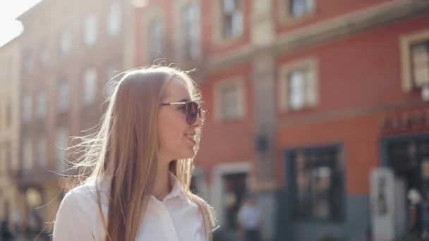 Die schöne Geschäftsfrau mit Sonnenbrille geht zu Fuß durch die Stadt. Blick auf den Stadtrand. Sommerzeit