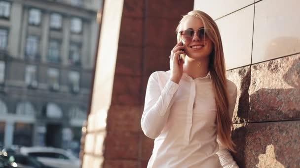 Fiatal üzletasszony állandó épület a napfényes város utcáin, és beszél a mobil cell phone office közelében. A napszemüveg használata mobiltelefon vonzó boldog lány a szabadban, naplemente