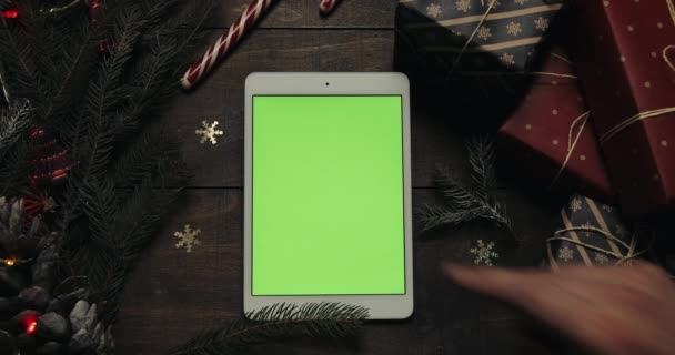 Férfi kezét megérinti oldalak a zöld képernyő fehér tabletta számítógép. Chroma-kulcs. Felülnézet. Függőleges helyzetben. Karácsonyi-újévi koncepció