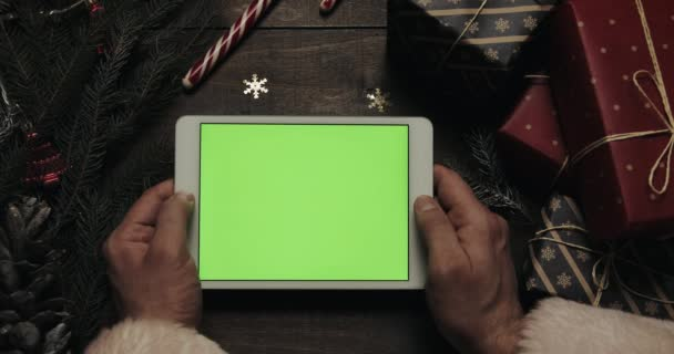 Férfi kezét megérinti oldalak a zöld képernyő fehér tabletta számítógép. Chroma-kulcs. Felülnézet. Függõlegesen a telefont. Karácsonyi-újévi koncepció
