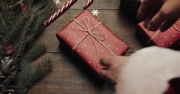 Rukou Santa Claus put dát velký novoroční dar ve stylu dřevěné pozadí s novoroční dekorace a vánoční strom s rozmazané blikající světla