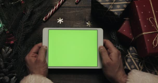 Santa Claus gazdaság oldalak fehér tabletta számítógép-val zöld képernyő kezében. Chroma-kulcs. Felülnézet. Függõlegesen a telefont. Karácsonyi-újévi koncepció