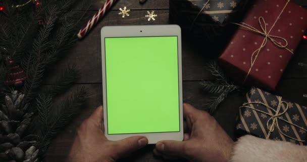 Santa Claus oldalak a fehér tabletta számítógép zöld képernyő megérintésével kezében. Más kezek, néhány jelenlegi doboz elhelyezése az asztalon. Chroma-kulcs. Felülnézet. Függőleges helyzetben. Karácsony-Szilveszter
