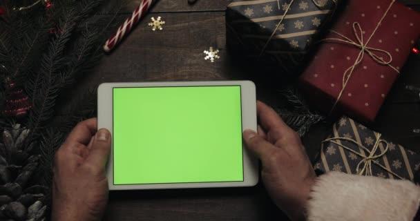 Rukou Santa Claus výčepní stránky v počítači bílou tabletu s zeleným plátnem. Jiné ruce umístění některé současné krabic na stole. Chromatický klíč. Pohled shora. Vánoce Nový rok internetové objednávky koncept