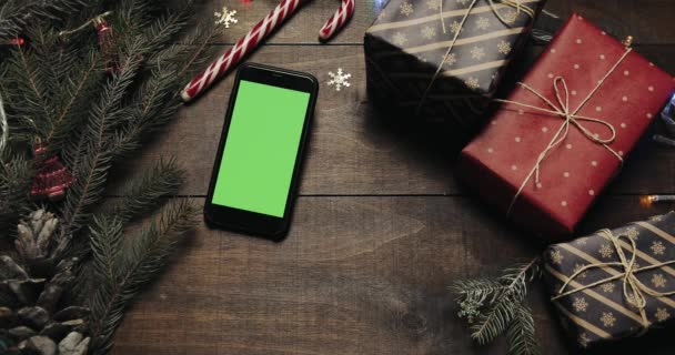 Top view. Black smartphone with green screen lying on the table with christmas holiday decoration. Hands of Santa Claus puts a gift on the table. Christmas holiday decoration top view concept
