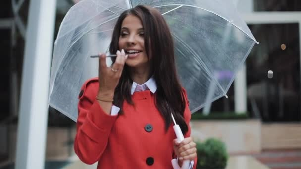 Photo Business lady in red coat sending audio voice message on smartphone at outdoor talking to mobile assistant. She holding umbrella in her hands. Girl using smartphone voice recognition.