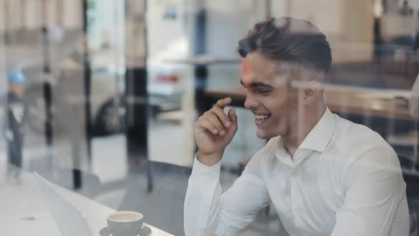 Young happy businessman talking on video conference call chat with a laptop in cafe. He laughs and fun jokes with his interlocutor. Successful people, daily routine