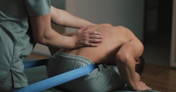 Alternative Medizin-Behandlung und Rehabilitation der Patienten. Physiotherapeut, Heilbehandlung auf mans Wirbelsäule mit blauen Gummiband