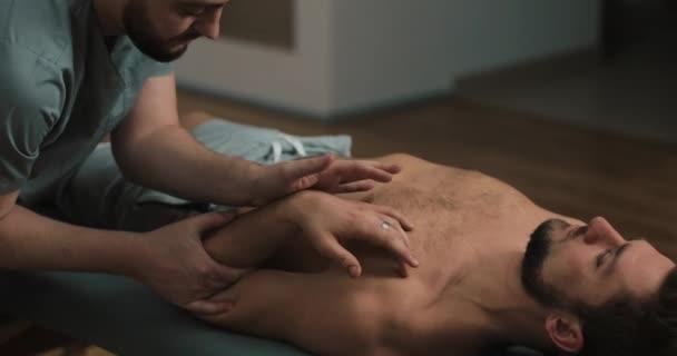 Fyzioterapeut dělá léčebná metoda na mans paže. Alternativní medicína léčba a rehabilitace pacientů