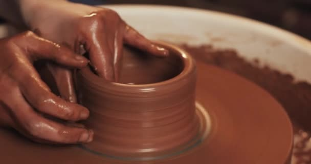 Potter creating a clay pot. Workshop of clay. Hands working on pottery wheel, shaping a clay pot. Red clay, close up.