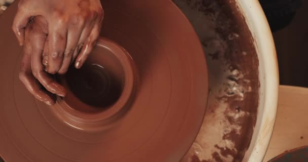Potter makes pottery from clay close up. Making ceramic products from red clay. Twisted potters wheel. Man hands making clay jug. Handmade, craft. Top view.