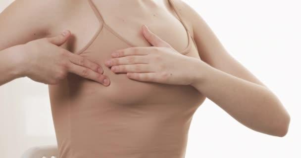 Žena kontroluje prs kvůli známkám rakoviny prsu. Zdravotní a savčí koncept. Zavřít.