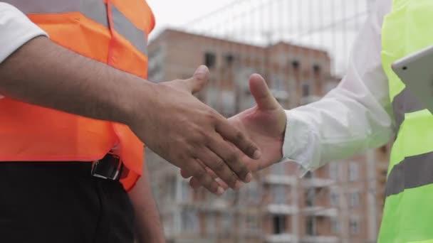 Zwei Architekten beim Händeschütteln auf der Baustelle. Nahaufnahme.