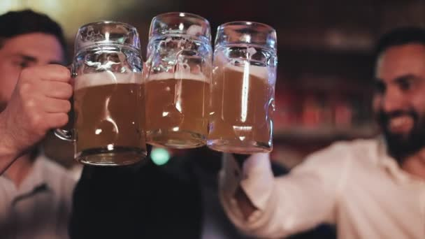 Három régi barátok csengő a szemüvegét a sör pub. Közelről, lassú mozgás. Ünnep sör Cheers koncepció.