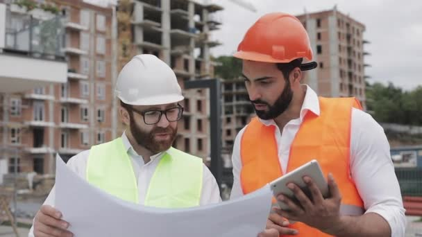 Building a residential complex or business center. Team of engineers men with a tablet and drawing analyzing plans construction builders job activity.