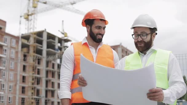 Ein lächelnder männlicher Bauingenieur diskutiert mit einem Architekten auf der Baustelle oder der Baustelle eines Hochhauses. sie halten Konstruktionszeichnungen in ihren Händen.