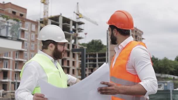 männliche Bauingenieur Diskussion mit Architekt auf der Baustelle oder auf der Baustelle eines Hochhauses. sie halten Konstruktionszeichnungen in ihren Händen.