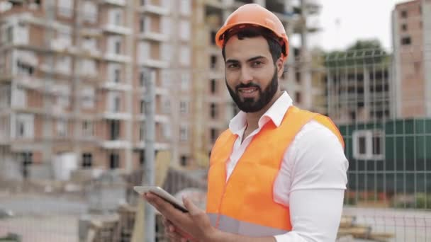 Portrait of construction worker on building site with tablet looking at the camera. Professions, construction, workers, architect concept.