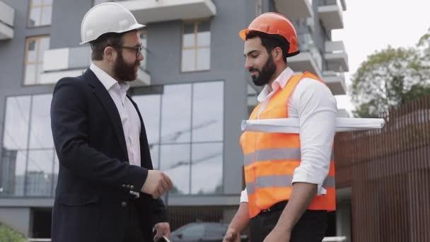 Vedoucí stavby a dělníci se třesou rukou na staveništi. Profese, stavebnictví, dělníci, koncepce architekta.