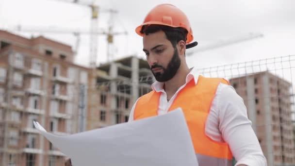Bauingenieur mit einem Projekt in der Hand. er prüft eine Zeichnung über den Hintergrund der Baustelle.
