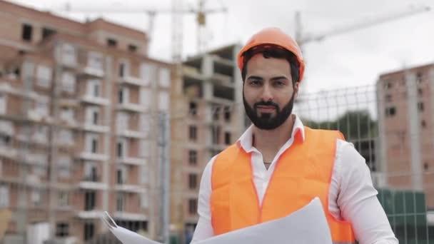 Portrét stavebního pracovníka z oranžové helmy a dívá se na kameru. Stavitel se stavebním projektem stojí na pozadí staveniště. Zpomaleně.