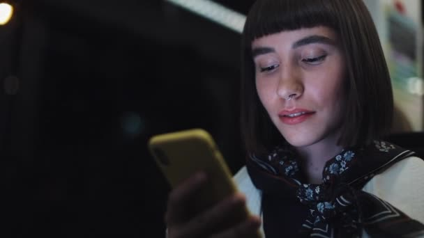 Hipsterová mladá žena, která používá smartphone při jízdě tramvají, byla zastřelena. Zpomaleně.