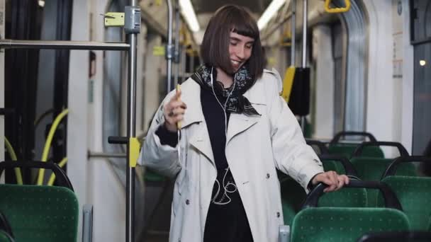 Portrait of young woman wearing in coat with headphones listening to music and funny dancing in public transport. He holds the handrail.